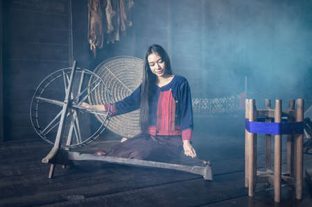 Young women demonstrate to procedure of making Thai Silk weaving in Thailand
