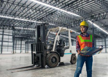 Femme travaillant avec un chariot élévateur dans un entrepôt. Banque d'images
