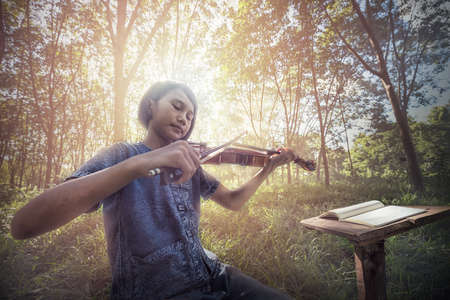 The musical, Little Asian child playing violin at outdoors 写真素材