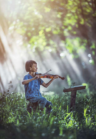 Little Asian child playing violin at outdoors