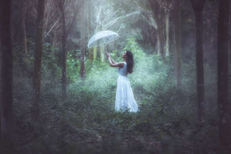 A girl with a white umbrella stands in forest.