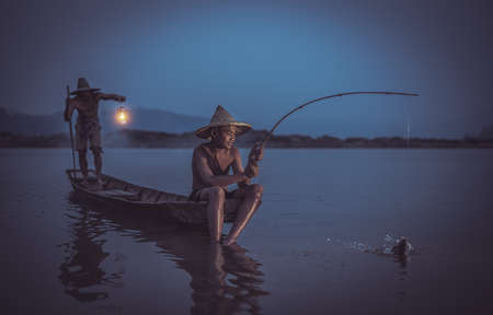 Children Fisherman with father catching fish on lake river Thailand