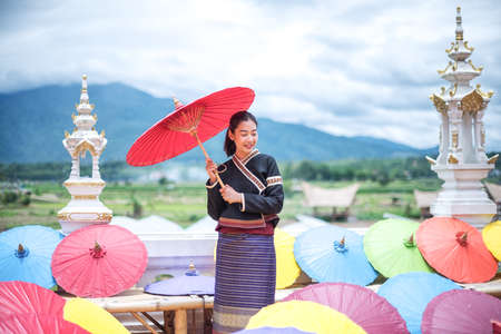 Portrait of Beautiful Thai Women in Lanna traditional costume, Handmade umbrella making vintage style in Thailand