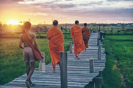 Buddhist monks on everyday morning traditional alms giving in Thailand.