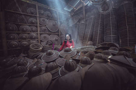 Asian female craftsman making the traditional hat in the old traditional house in Inle lake village, Shan State, Myanmar, traditional artist concept