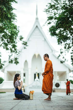 Thai woman with traditional dress sit pray respect monk, present buddhism people Make merit with monk that representative of Buddha. Woman Make merit by offering food to monk