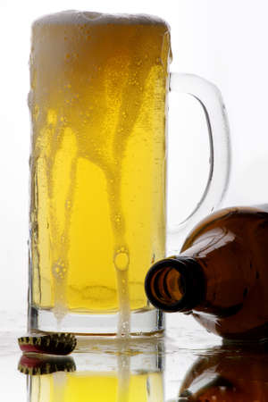 Beer foam flows down on a glass mug photo