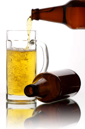 Beer flows from a bottle in a mug photo