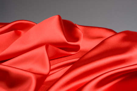 Bright red fabric waves on a grey background photo