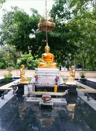 Golden buddha and disciples statue in the park. Stock Photo