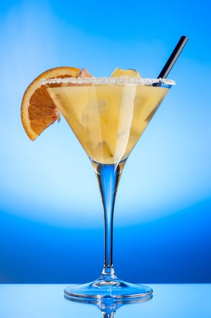 margarita glass: Glass of margarita with ice cubes and a slice of orange over a light blue background