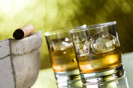 unhealthful: Two glasses of wiskey with ice cubes and a cigar Stock Photo