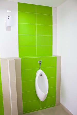 Urinal in the bathroom with a green wall  photo