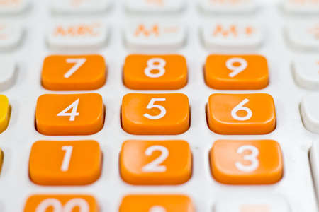 Taxation concept - Orange calculator with the word TAX added acr Stock Photo