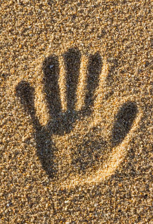 handprint in the sand of a beach  photo