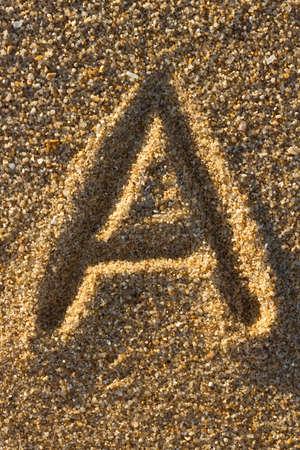 versatile: Alphabet letters in sand on beach  Stock Photo