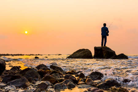 fishingpole: Fisherman standing on a rock at dawn sky background
