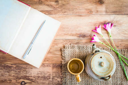 Tea cups with teapot with open book on old wooden table. Top view. Stockfoto