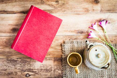 book: Čajové šálky s konvice s červenou knihu na starý dřevěný stůl. Pohled shora.