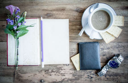 office time: cup of coffee on rustic wooden table with open books Stock Photo