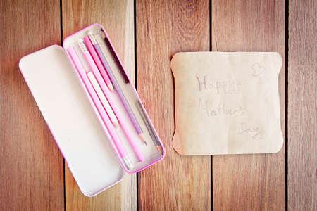agradecimiento: Tarjeta Día de la Madre con lápices de caja sobre una tabla de madera. Foto de archivo