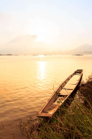 puesta de sol: Canoa por el r�o Mekong al amanecer. Foto de archivo