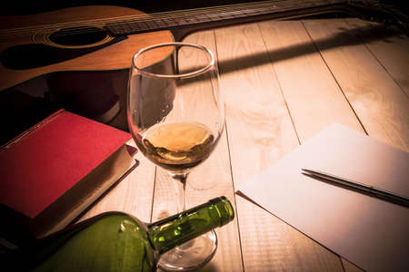 wine glasses: Guitar with Red Book and Wine on a wooden table. Stock Photo