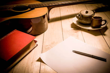 sheet music background: Guitar with Red Book and pen on a wooden table, Vintage style.