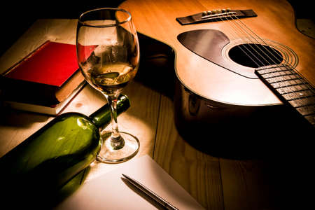 grunge music background: Guitar with Red Book and Wine on a wooden table. Stock Photo