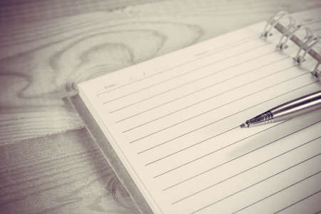 open spaces: Blank white notebook and pen with copyspace on wood background, Vintage Style. Stock Photo