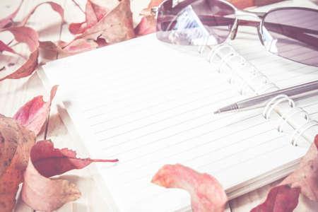 hojas secas: cuaderno en blanco con la pluma en la mesa de madera y hoja seca, concepto de negocio. Foto de archivo