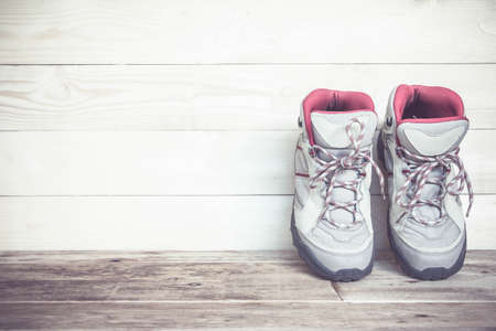 work boots: Pair of work boots on wooden background. Stock Photo