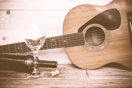 vintage Guitar with wine bottle and glass on the old wood floor. Reklamní fotografie - 44171454