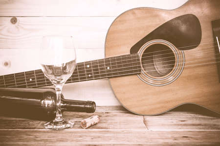 vintage music: vintage Guitar with wine bottle and glass on the old wood floor.