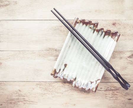 desk tidy: Empty plate and chopsticks on wooden table Stock Photo