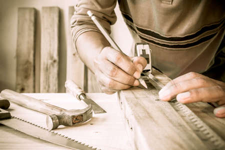 the throughout: Precision throughout. Serious young male carpenter working with wood in his workshop