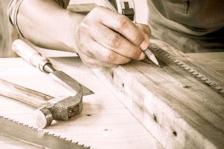 herramientas de trabajo: Cierre de vista de un carpintero utilizando una regla para dibujar una l�nea en un tablero. Foto de archivo
