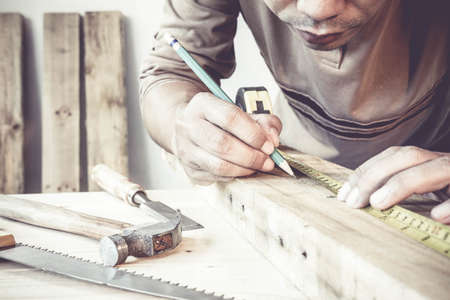 Serious young male carpenter working with wood in his workshop. Stockfoto
