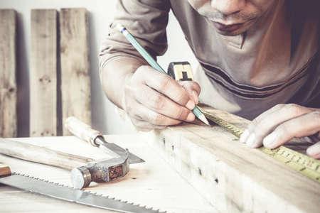 menuisier: Sérieux charpentier jeune mâle travail du bois dans son atelier. Banque d'images