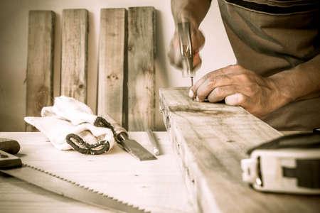 carpenter hammer a nail, vintage style. Stock Photo