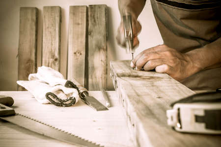 rolledup sleeves: carpenter hammer a nail, vintage style. Stock Photo