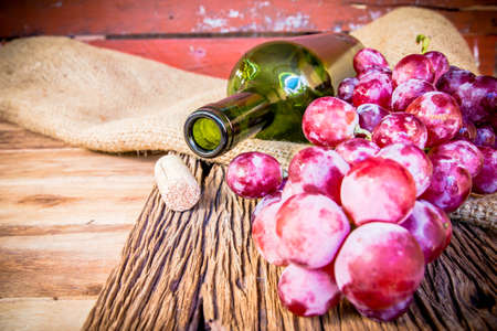 des vins: Bottle of red wine, grape and corks on wooden table.