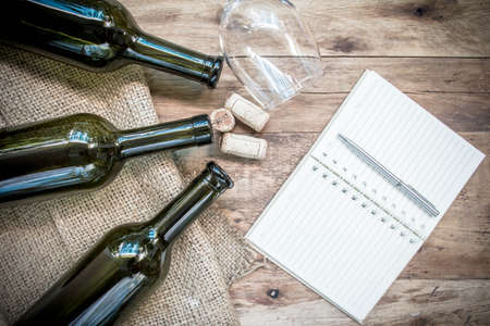 closed corks: Red wine bottle, glass and grape shaped corks and open book on wooden table.