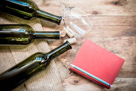 closed corks: Red wine bottle, glass and grape shaped corks and red book on wooden table.