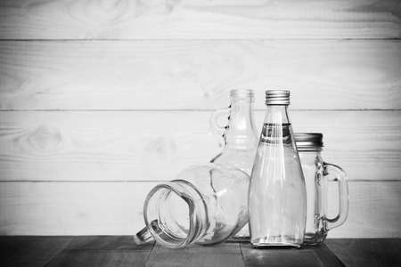 white washed: assorted glass bottles on a white washed wooden table. Clear glass bottles and containers of various sizes and shapes. Black & white. Stock Photo
