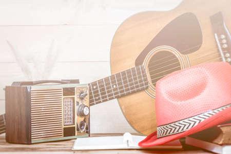 transistor: Antiguo radio de transistores y la guitarra ac�stica en el fondo de madera, hecho con filtros de color, enfoque borroso. Estilo retro.