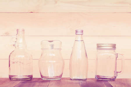 white washed: assorted glass bottles on a white washed wooden table. Clear glass bottles and containers of various sizes and shapes. Retro Style.