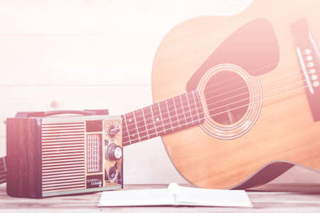 transistor: Old transistor radio and Acoustic guitar on wooden background, made with color filters,blurred focus. Retro Style.