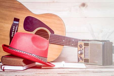transistor: Antiguo radio de transistores y la guitarra acústica en el fondo de madera, hecho con filtros de color, enfoque borroso. Estilo retro.