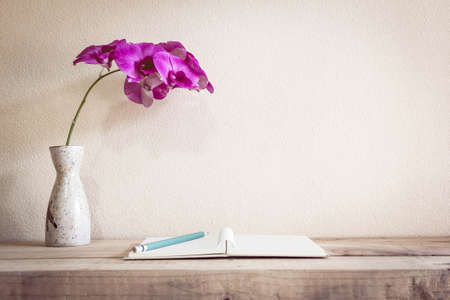 Open book with pencil and Flowers, home decoration concept.